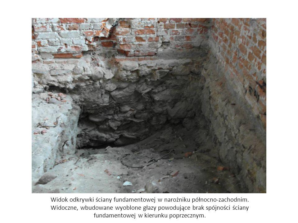 Widok odkrywki ściany fundamentowej w narożniku północno-zachodnim. Widoczne, wbudowane wyoblone głazy powodujące brak spójności ściany fundamentowej