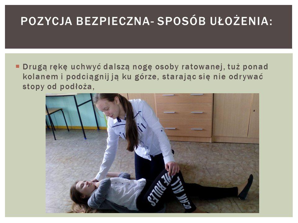  Drugą rękę uchwyć dalszą nogę osoby ratowanej, tuż ponad kolanem i podciągnij ją ku górze, starając się nie odrywać stopy od podłoża, POZYCJA BEZPIECZNA- SPOSÓB UŁOŻENIA: