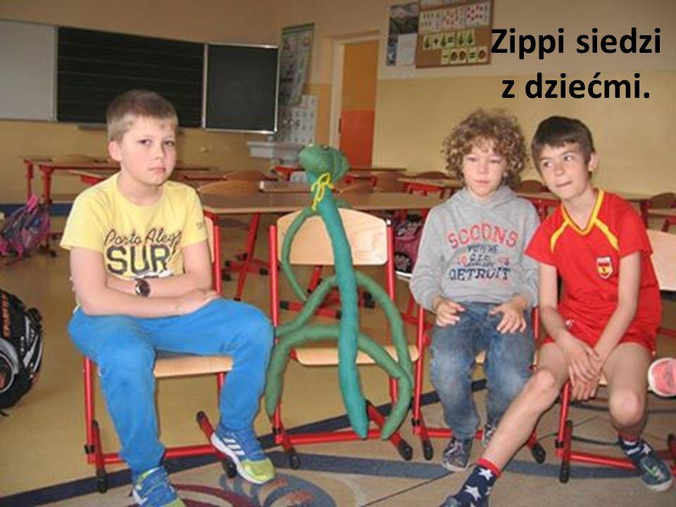 Zippi siedzi z dziećmi.