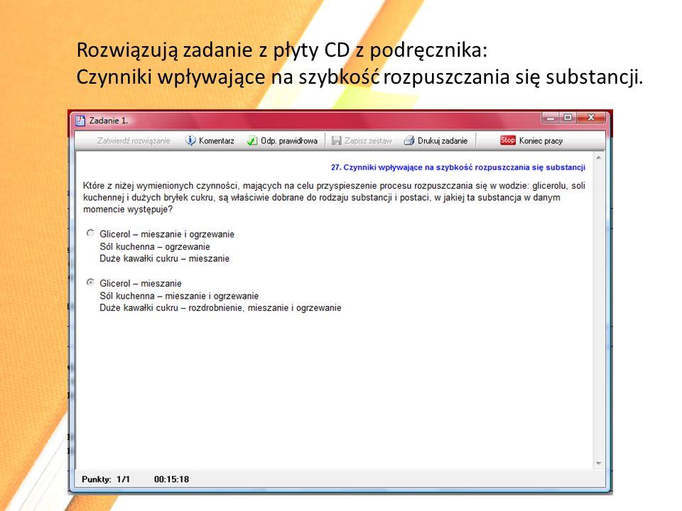 Rozwiązują zadanie z płyty CD z podręcznika: Czynniki wpływające na szybkość rozpuszczania się substancji.