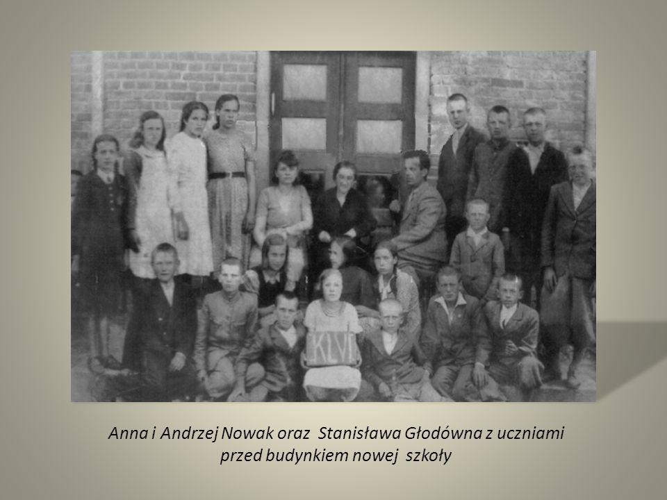 Anna i Andrzej Nowak oraz Stanisława Głodówna z uczniami przed budynkiem nowej szkoły