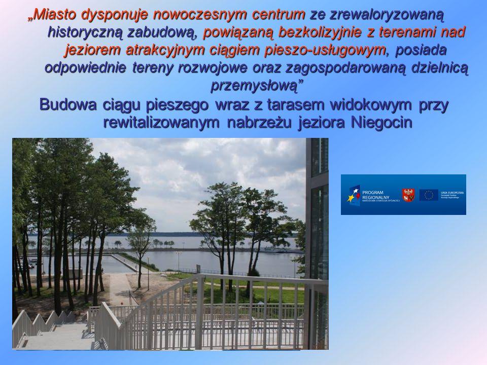 """""""Miasto dysponuje nowoczesnym centrum ze zrewaloryzowaną historyczną zabudową, powiązaną bezkolizyjnie z terenami nad jeziorem atrakcyjnym ciągiem pieszo-usługowym, posiada odpowiednie tereny rozwojowe oraz zagospodarowaną dzielnicą przemysłową Budowa ciągu pieszego wraz z tarasem widokowym przy rewitalizowanym nabrzeżu jeziora Niegocin"""