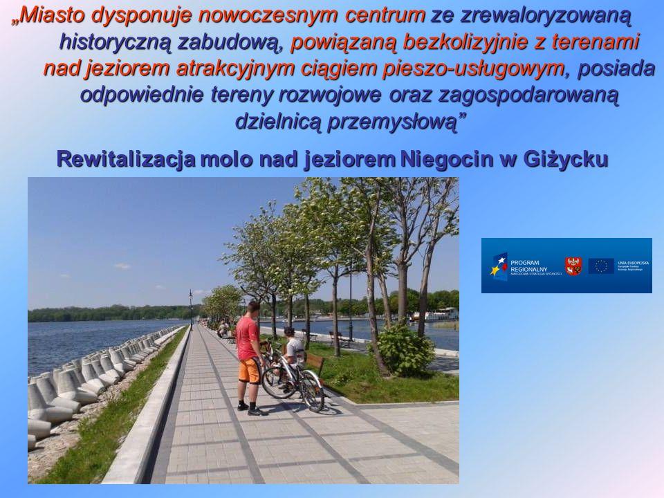 """""""Miasto dysponuje nowoczesnym centrum ze zrewaloryzowaną historyczną zabudową, powiązaną bezkolizyjnie z terenami nad jeziorem atrakcyjnym ciągiem pieszo-usługowym, posiada odpowiednie tereny rozwojowe oraz zagospodarowaną dzielnicą przemysłową Rewitalizacja molo nad jeziorem Niegocin w Giżycku"""