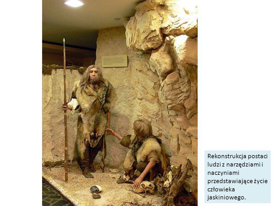 Rekonstrukcja postaci ludzi z narzędziami i naczyniami przedstawiające życie człowieka jaskiniowego.