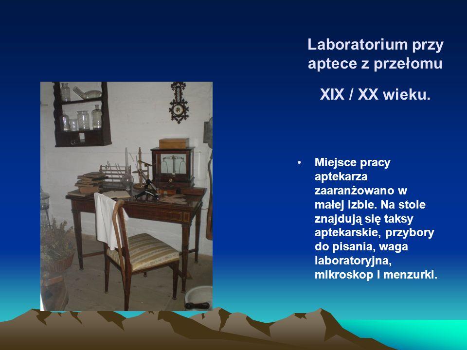 Laboratorium przy aptece z przełomu XIX / XX wieku. Miejsce pracy aptekarza zaaranżowano w małej izbie. Na stole znajdują się taksy aptekarskie, przyb