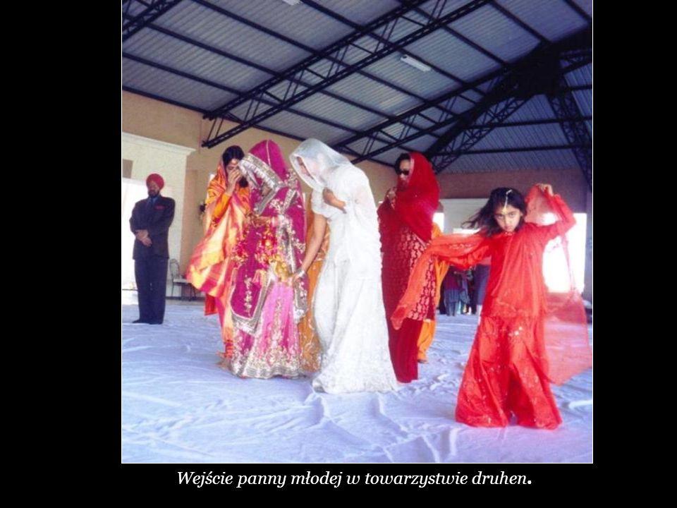 Panna młoda obchodzi ołtarz. Jest prowadzona kolejno przez 4 mężczyzn stojących w 4 rogach ołtarza.