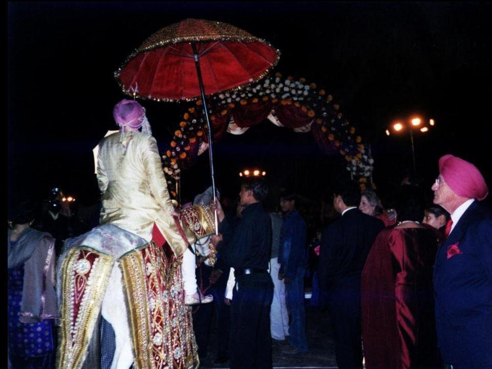 Pan młody wchodzi przez łuk ozdobiony kwiatami i czeka na rodzinę oblubienicy.