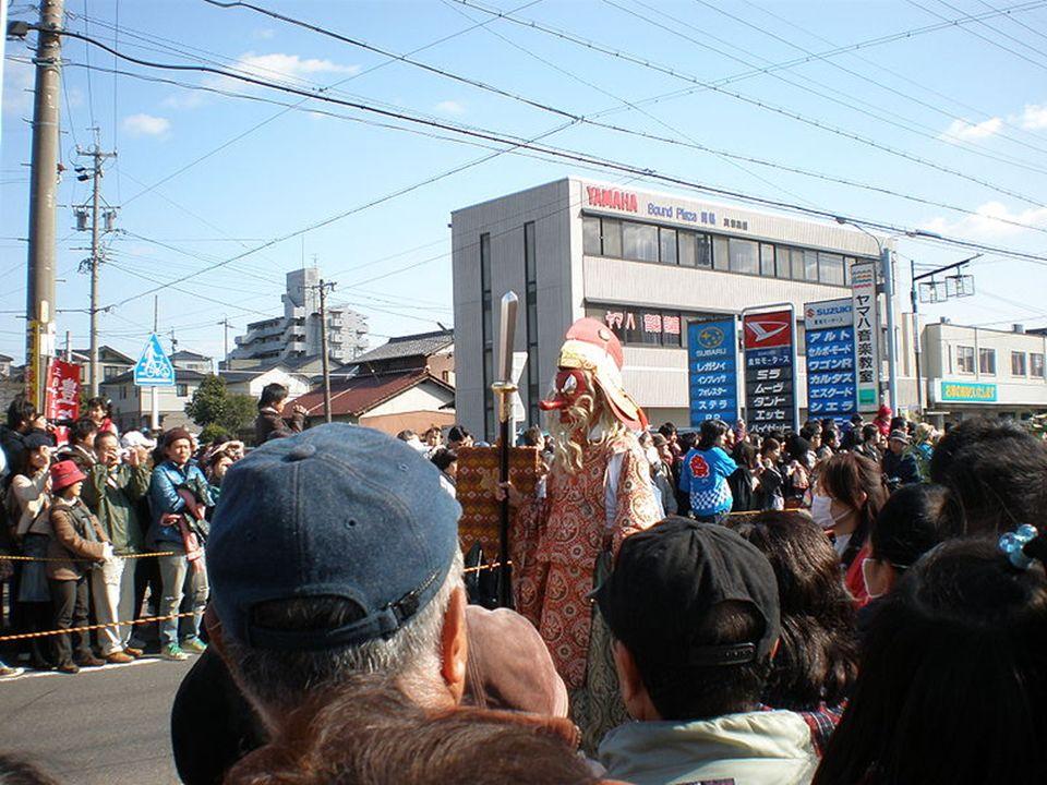 Za nimi podąża grupa shintoistycznych kapłanów, wśród których znajduje się osoba nosząca maskę z charakterystycznym długim nosem i włosami w nieładzie, reprezentująca boga Sarutahiko.
