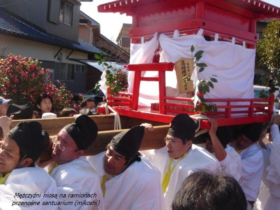 Za kapłanami z drzewkami podążają dwaj mieszkańcy niosący kufer zawierający dary z ryżu i sake oraz kamienie o fallicznym kształcie.