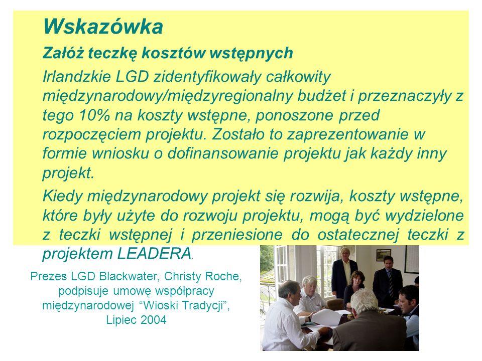 Prezes LGD Blackwater, Christy Roche, podpisuje umowę współpracy międzynarodowej Wioski Tradycji , Lipiec 2004 Wskazówka Załóż teczkę kosztów wstępnych Irlandzkie LGD zidentyfikowały całkowity międzynarodowy/międzyregionalny budżet i przeznaczyły z tego 10% na koszty wstępne, ponoszone przed rozpoczęciem projektu.