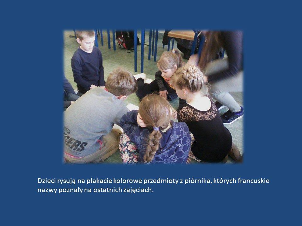 Dzieci rysują na plakacie kolorowe przedmioty z piórnika, których francuskie nazwy poznały na ostatnich zajęciach.