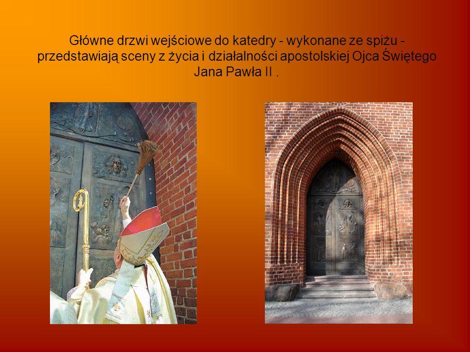 Główne drzwi wejściowe do katedry - wykonane ze spiżu - przedstawiają sceny z życia i działalności apostolskiej Ojca Świętego Jana Pawła II.