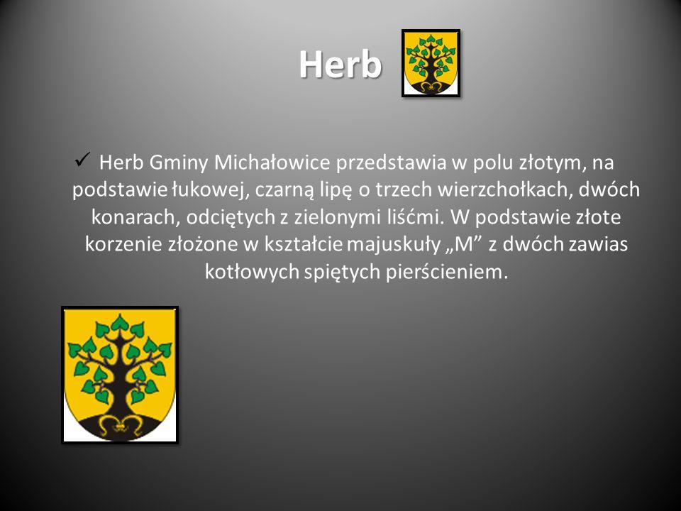 Herb Herb Gminy Michałowice przedstawia w polu złotym, na podstawie łukowej, czarną lipę o trzech wierzchołkach, dwóch konarach, odciętych z zielonymi liśćmi.