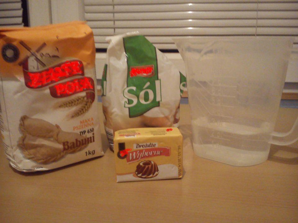 Wsyp mąkę do dużej miski (najlepiej do dzieży stojącego miksera), zrób pośrodku wgłębienie, dodaj drożdże, sól, wodę i wyrabiaj ciasto ręcznie lub hakiem miksera, aż będzie miękkie i elastyczne (ok 10 minut).