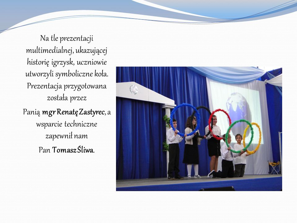 Na tle prezentacji multimedialnej, ukazującej historię igrzysk, uczniowie utworzyli symboliczne koła. Prezentacja przygotowana została przez Panią mgr