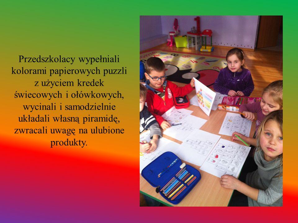 Przedszkolacy wypełniali kolorami papierowych puzzli z użyciem kredek świecowych i ołówkowych, wycinali i samodzielnie układali własną piramidę, zwracali uwagę na ulubione produkty.
